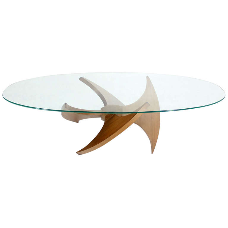 glass-top-oval-coffee-table-shaped-table-top-serves-as-a-dinner-table-for-a-family-of-two-or-three-it-is-a-simple-modern-walnut-propeller-base (Image 8 of 9)