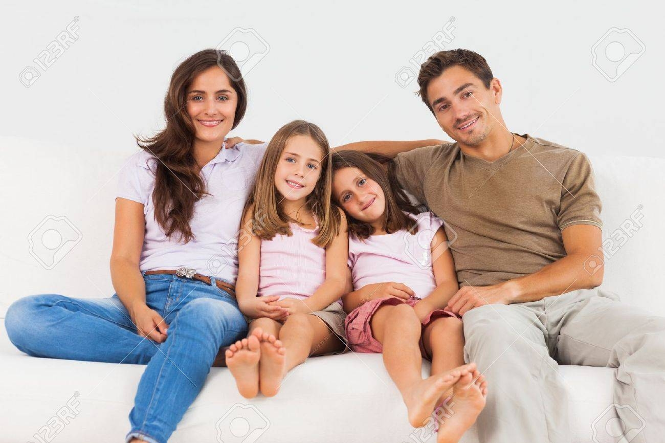 Cute Family Sitting On A Sofa In The Living Room Stock Photo within Family Sofa (Image 3 of 30)