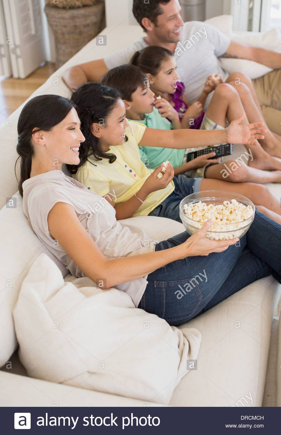 Family Watching Movie On Sofa In Living Room Stock Photo, Royalty intended for Family Sofa (Image 15 of 30)