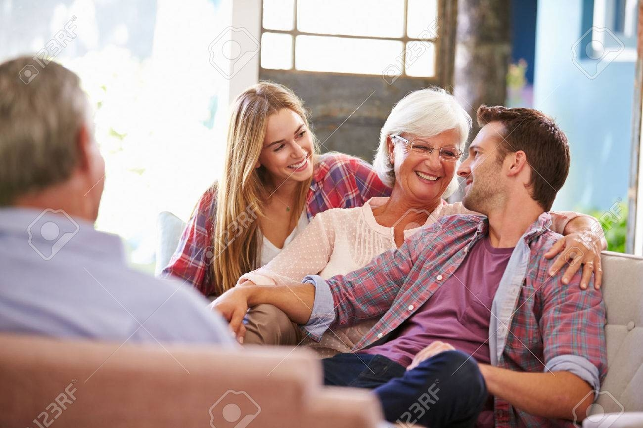Family With Adult Children Relaxing On Sofa At Home Together Stock with regard to Family Sofa (Image 16 of 30)