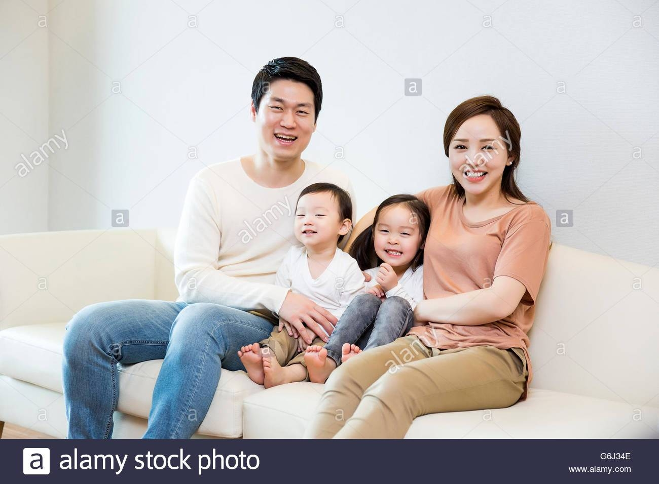 Happy Asian Family Smiling On The Sofa At Home Stock Photo intended for Family Sofa (Image 21 of 30)
