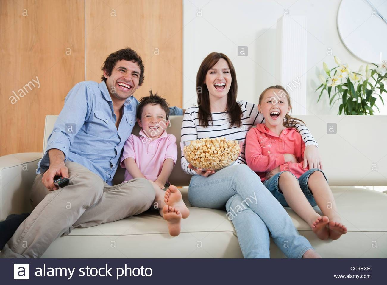 Laughing Family Watching Tv On Sofa Stock Photo, Royalty Free with regard to Family Sofa (Image 28 of 30)