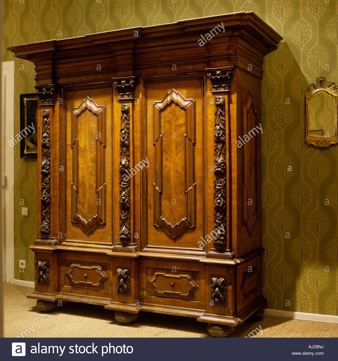 Ornate Antique Wooden Wardrobe With Green Patterned Wallpaper with regard to Ornate Wardrobes (Image 12 of 15)