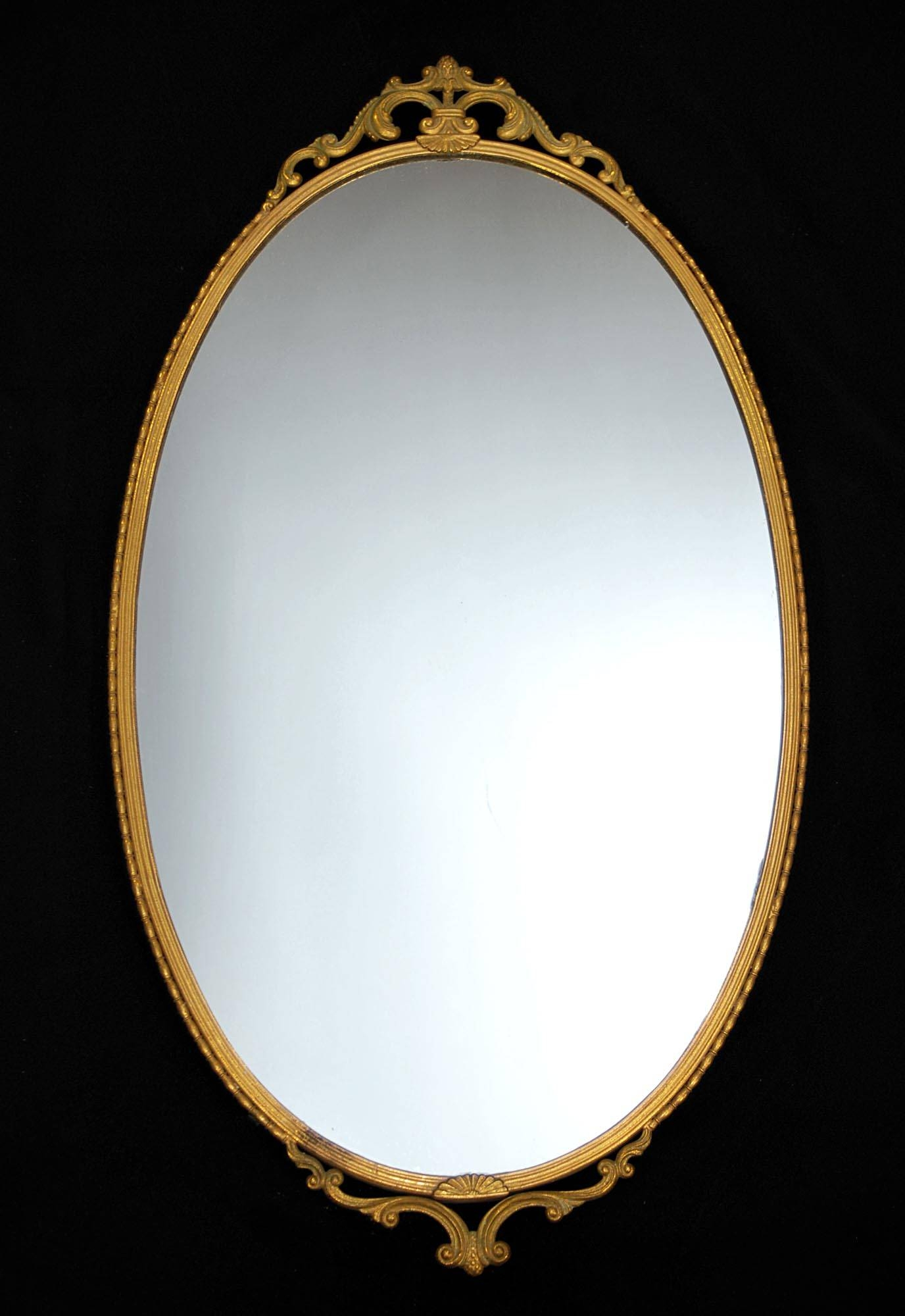 Oval Mirror With Golden Steel Frame Placed On The Black Wall Of with regard to Black Oval Wall Mirrors (Image 15 of 25)