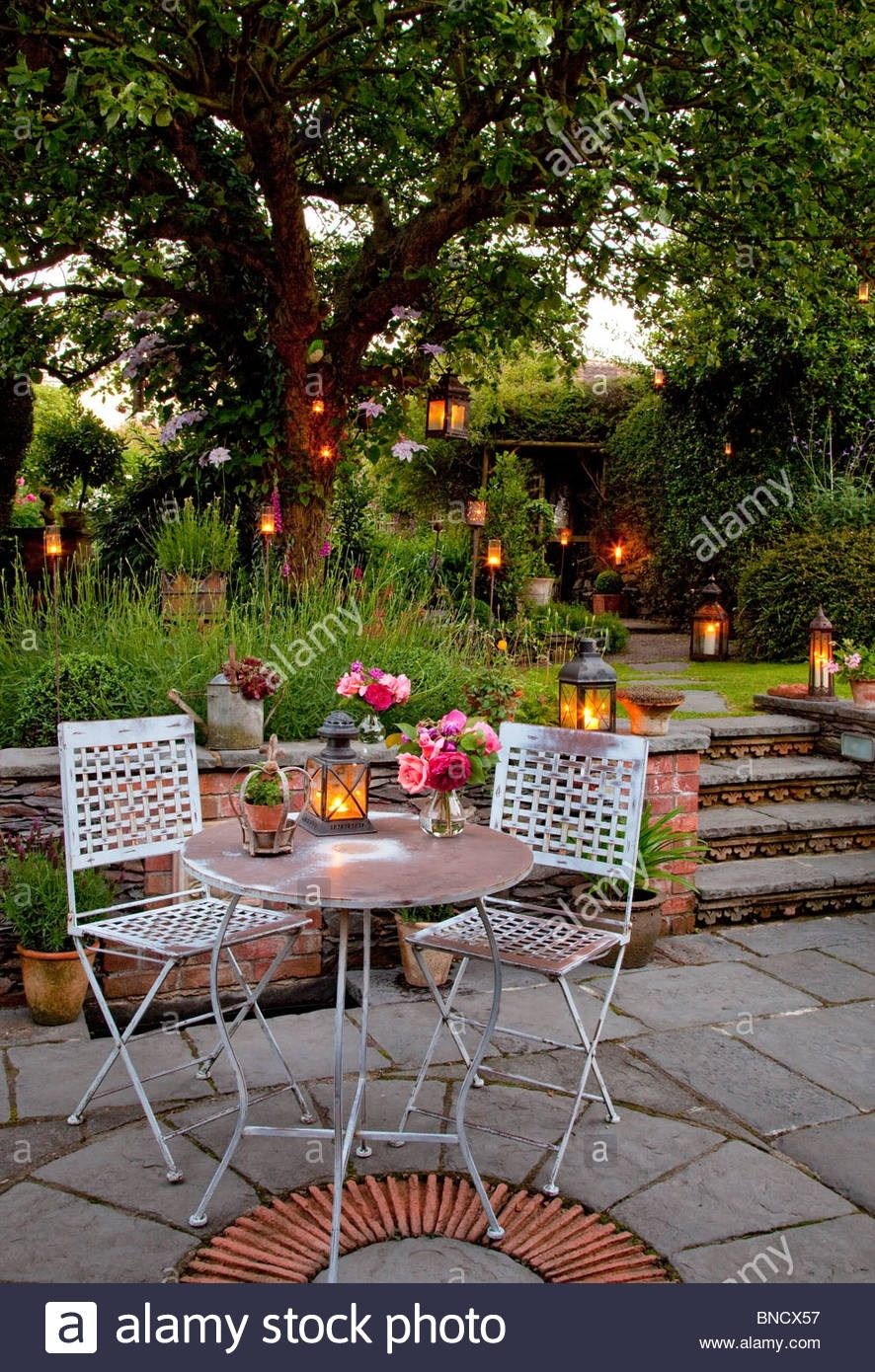 Metal Table And Chairs On Patio With Candles And Lanterns In Garden for Outdoor Table Lanterns (Image 9 of 20)