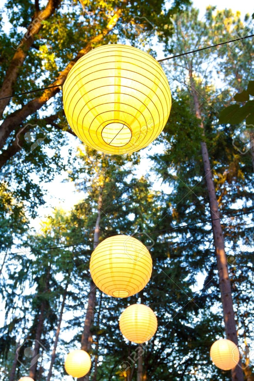 Yellow Wedding Decorations Hang From The Trees At A Wedding Ceremony Pertaining To Outdoor Hanging Japanese Lanterns (Photo 14 of 20)